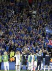 Iceland players and their supporters celebrate at the end of the Euro 2016 Group F soccer match between Portugal and Iceland at the Geoffroy Guichard stadium in Saint-Etienne, France, Tuesday, June 14, 2016. (AP Photo/Pavel Golovkin)